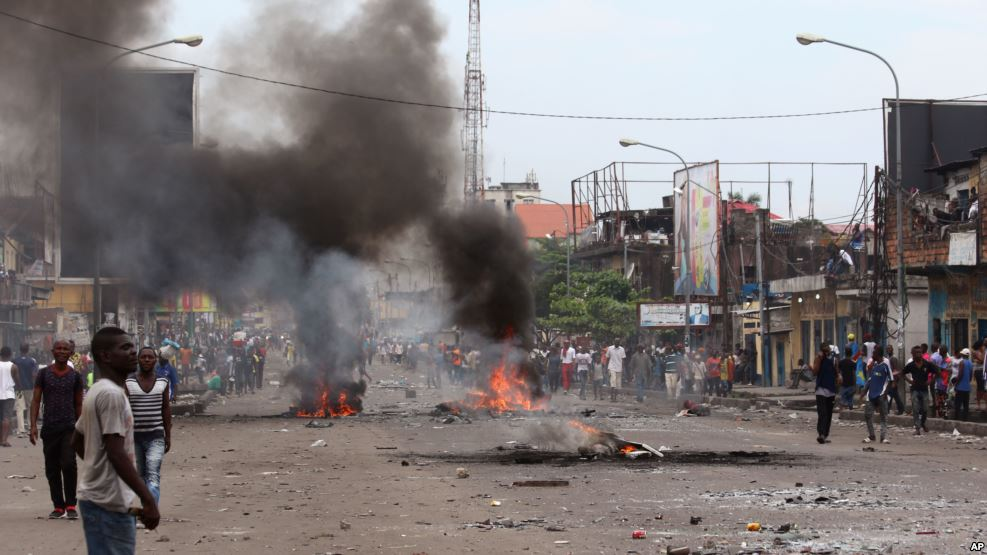 A man crosses a road near burning debris, during election protests in Kinshasa, Democratic Republic of Congo, Monday, Sept. 19, 2016.