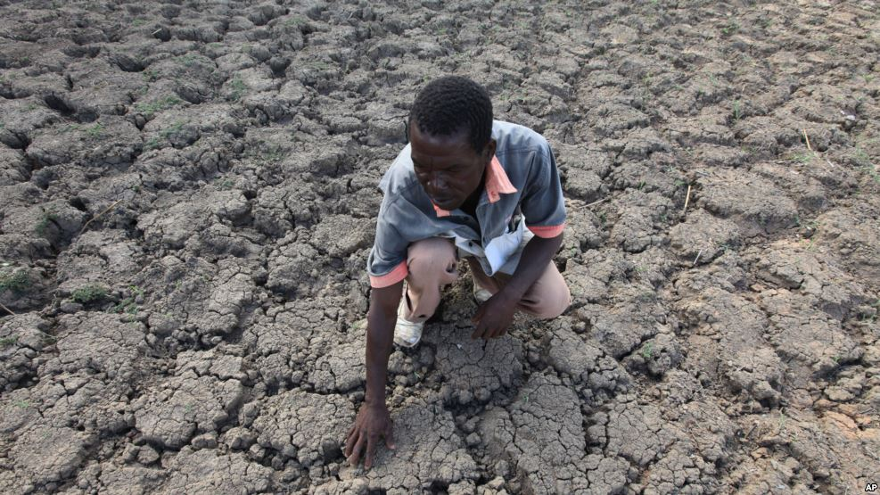 FILE - Last Zimaniwa feels the broken ground at a spot which is usually a reliable water source that has dried up due to lack of rains in the village of Chivi , Zimbabwe, Jan. 29, 2016. Southern Africa's lengthy drought has gotten worse, aid officials say